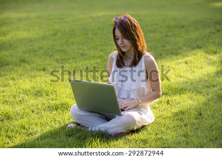 Nice young woman using her notebook in the park. - stock photo