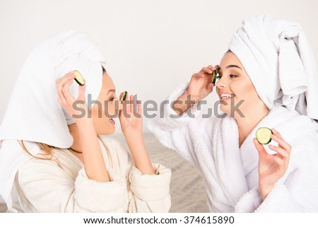 Nice young women with cucumbers on eyes and towel on their heads - stock photo