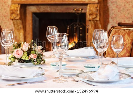 nicely arranged table next to the fireplace - stock photo