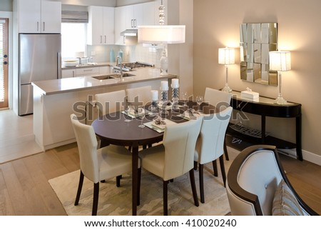 Nicely decorated and served living, lunch room dining table with the kitchen at the back. Interior design. - stock photo