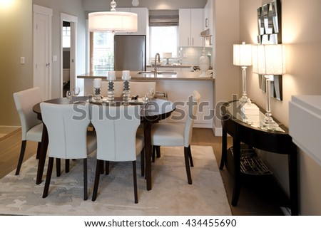 Nicely decorated and served living, lunch  room table with the kitchen at the back. Interior design. - stock photo