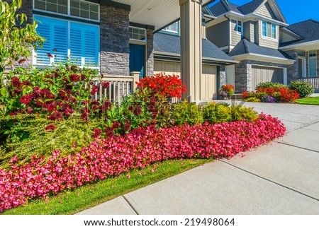 Nicely decorated colorful flowerbed and trimmed front yard lawn in front of the house at the pedestrian sidewalk. Landscape design. - stock photo