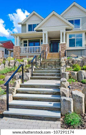 Nicely decorated house entrance. Stone steps leading to the house. Landscape design - stock photo