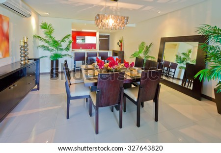 Nicely decorated luxury modern living, dining suite: dining room with the table and some chairs and and the kitchen at the back. Interior design. - stock photo