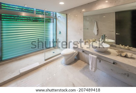 Nicely decorated modern luxury modern washroom. Marble shelf and sink, toilet and bathroom with rain shower head. Interior design. - stock photo