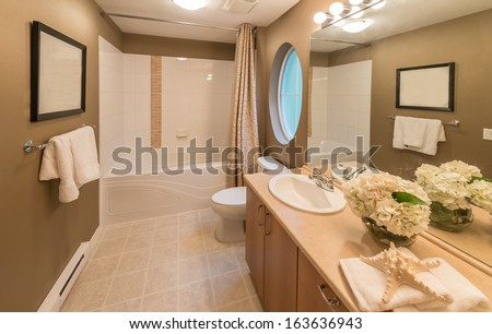 Nicely decorated modern washroom, bathroom with the toilet sit, sink, some plants on the shelf and vase with flowers. Interior design.