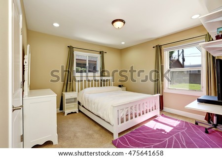 Nicely furnished bedroom in small American craftsman style home. Accent color home design. Green olive window curtains and purple rug. Northwest, USA