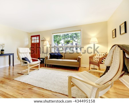 Nicely furnished living room with entryway red door, hardwood floor and beige walls. - stock photo