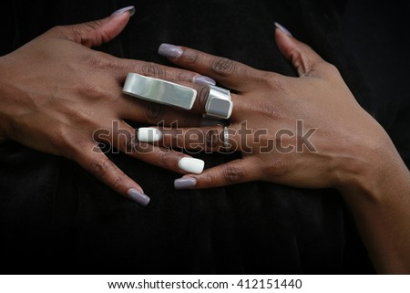 Nicely manicured hands of African-American woman with cast for arthritis or fractured finger - stock photo