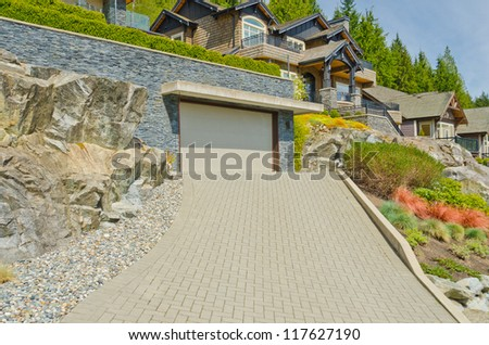 Nicely paved driveway to the garage with double door. - stock photo