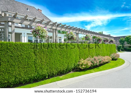 Nicely trimmed green fence with big custom made luxury house behind in the suburbs of Vancouver, Canada. Keeps privacy and security. Landscape trimming design. - stock photo
