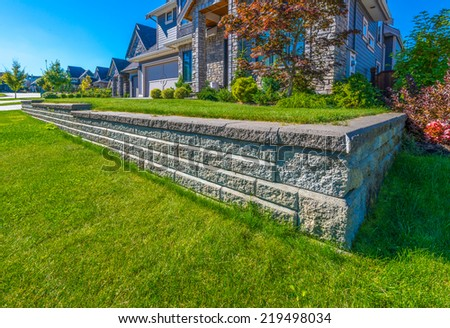 Nicely trimmed lawn grass on the leveled and stoned front yard. Landscape design. - stock photo