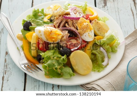 nicoise salad over wood background - stock photo