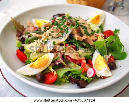 Nicoise Salad served in a restaurant in Cannes, France. Horizontal, tilted view