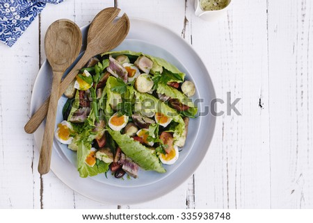 nicoise salad with a small pot of dressing and copyspace - stock photo