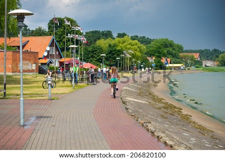 NIDA - JULY 14: Tourists walking along the pedestrian way the small resorts and villages is situated one after the one near the coast of Curronian Lagoon on July 14, 2014 in Nida, Lithuania.