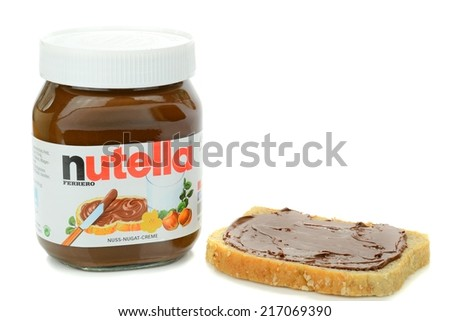 NIEDERSACHSEN, GERMANY SEPTEMBER 13, 2014: A glass jar of Ferrero Nutella chocolate spread and a slice of wholemeal bread on a white background - stock photo