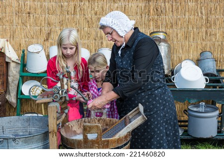 NIEUWEHORNE, THE NETHERLANDS - SEP 27: Farmer woman shows two children the use of a traditional washhub during the agricultural festival Flaeijel on September 27, 2014, the Netherlands
