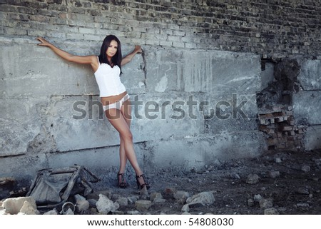 Nifty lady in the lingerie standing in old ruins
