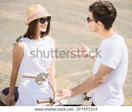 Nifty young couple talking to each other and smiling while woman sitting on scooter. Weekend together. - stock photo