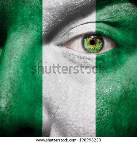 Nigerian flag painted on a man's face to show support for Nigeria - stock photo