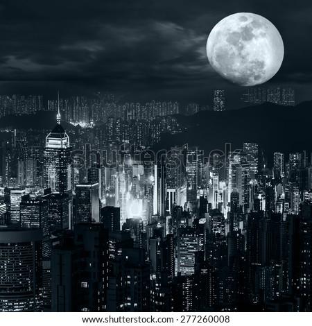 Night aerial view panorama of Hong Kong skyline at full moon night under dramatic cloudy sky - stock photo