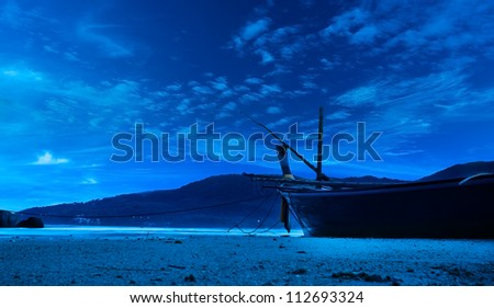 Night beach landscape background. Old fishing boat in blue moonlight - stock photo