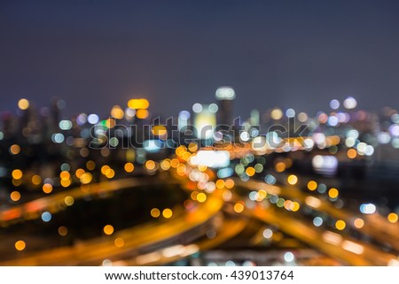 Night blurred lights, city road interchanged and office building background - stock photo