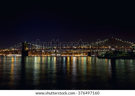 Night Brooklyn Bridge with lights and reflection in water - stock photo