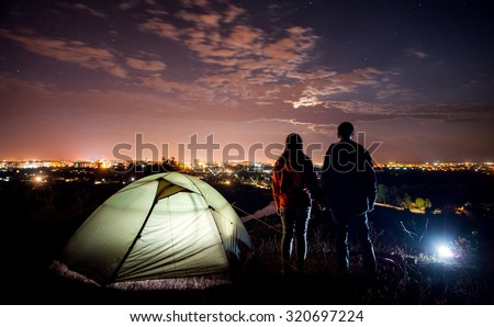 night camping near the town. a young couple holding hands and looking at night city - stock photo