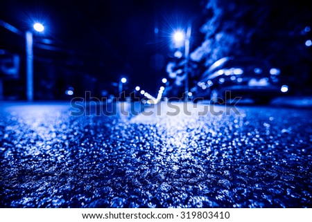 Night city after rain, parked the car at the roadside. View from a wide angle at the level of the asphalt, image in the blue toning - stock photo