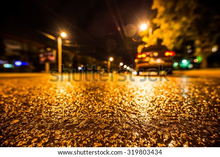 Night city after rain, parked the car at the roadside. View from a wide angle at the level of the asphalt - stock photo