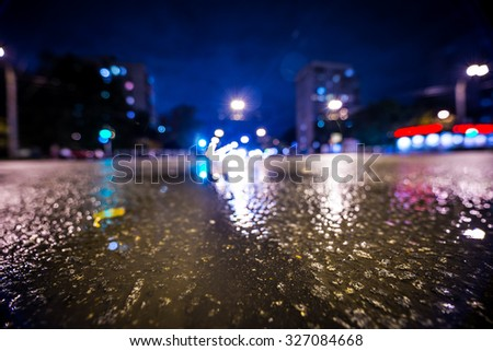 Night city after rain, the glowing lights of approaching cars. Wide angle view of the level of puddles on the pavement, in blue tones - stock photo