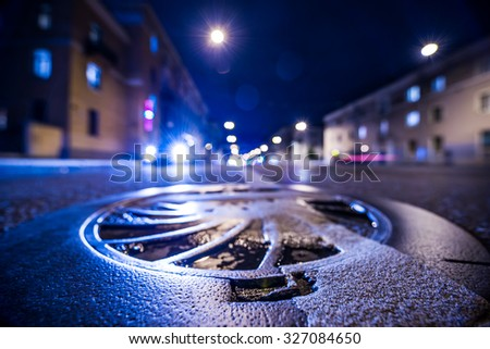 Night city after rain, the glowing lights of approaching cars. Wide angle view of the level of a manhole on the pavement, in blue tones - stock photo