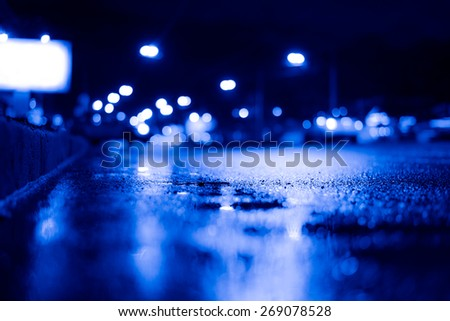 Night city after rain, view of the flow of cars from the curb, billboard stands on the sidelines. Image in the blue toning - stock photo