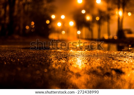 Night city alley with lanterns in the fog after rain. View from the level of asphalt, in yellow tones - stock photo