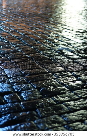 Night city. Closeup of wet cobblestone at night after rain