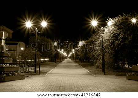 night city lane with burning street lamps in sepia tone - stock photo
