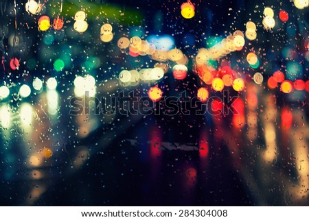 night city life through windshield: cars, lights and rain