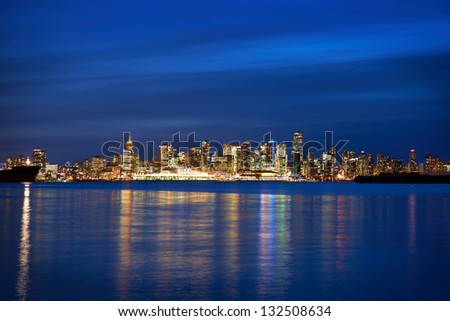 Night city, panoramic scene of downtown reflected in blue water. Vancouver, Canada - stock photo