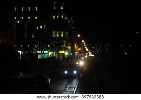 Night city road  with tram rails lit by lanterns, headlights of cars and light from the windows of buildings bokeh background - stock photo