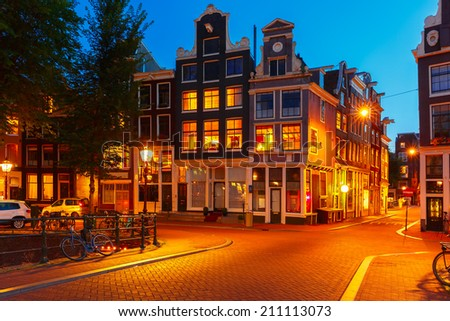 Night city view of Amsterdam bridge and typical dutch houses, Holland, Netherlands.