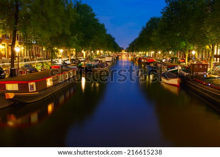 Night city view of Amsterdam canal and typical Houseboat, Holland, Netherlands.  - stock photo