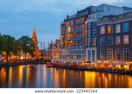 Night city view of Amsterdam canal, bridge and Munttoren tower, Holland, Netherlands.