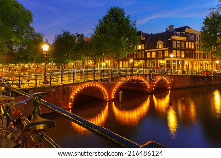 Night city view of Amsterdam canal, bridge and typical houses, boats and bicycles, Holland, Netherlands.  - stock photo