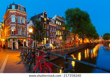 Night city view of Amsterdam canal, bridge with typical houses and bicycles, Holland, Netherlands. - stock photo