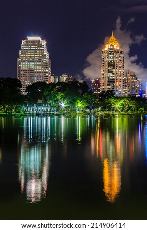 Night cityscape, office buildings with reflection in Thailand at dusk. View from public park.