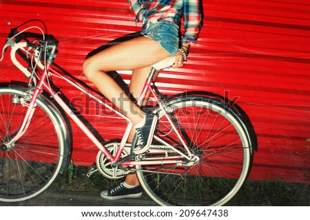 Night flash light picture of bicycle riding sexy girl in summer on red background urban style vintage bike  - stock photo