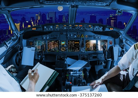 Night flight inside a cockpit flying on New York skyline of United States of America.. Pilots arms and blank white papers for copy space - stock photo