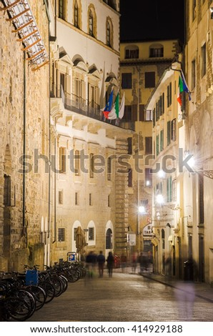 Night Florence street with old renaissance stone buildings, parked bicycles and people passing by. Flags of EU, Italy and Florence are waving on a balcony of house with green wooden window shutters - stock photo